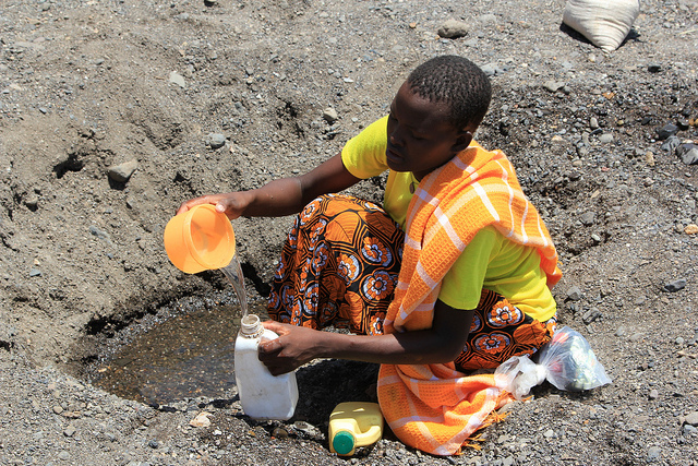 A woman in Kenya digs drinking water out of the sand.